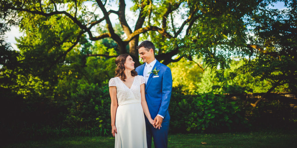 A bride in her wedding dress looks up at her groom, in a blue suit, with affection. They hold hands in a lush park.