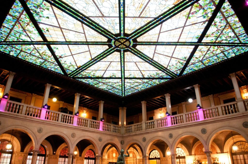 A ballroom with a stained glass skylight over an Italian Neo-Renaissance arcade.