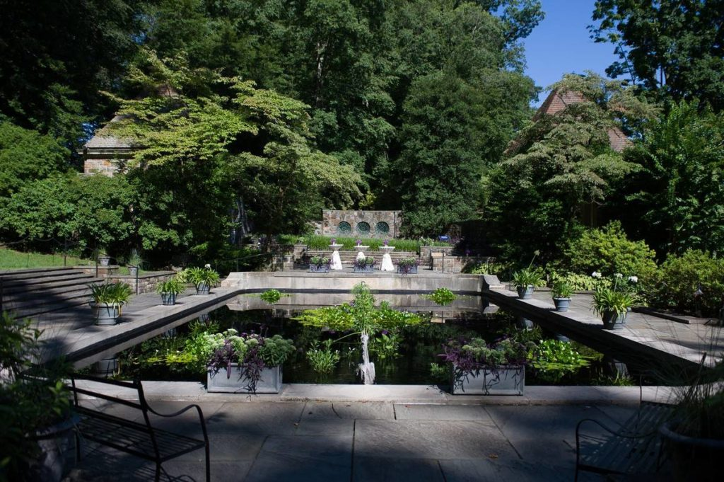 A reflecting pool surrounded by benches and lush greenery.